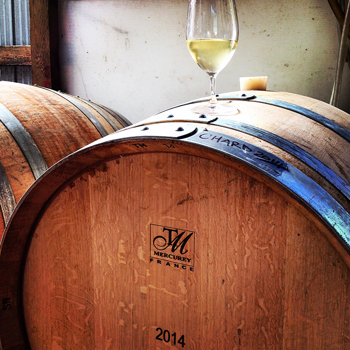 Wine barrel containing 2014 Chardonnay with a single glass resting on top
